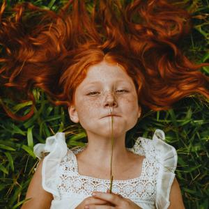 Meisje met rood haar en sproeten in het gras. Rood haar en sproeten gaan samen omdat beide uit hetzelfde stukje DNA komen